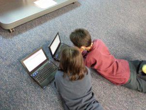 portable ordinateur fille jouer sol garçon séance enfant éducation Enfants bambin apprentissage collaboration Positions humaines
